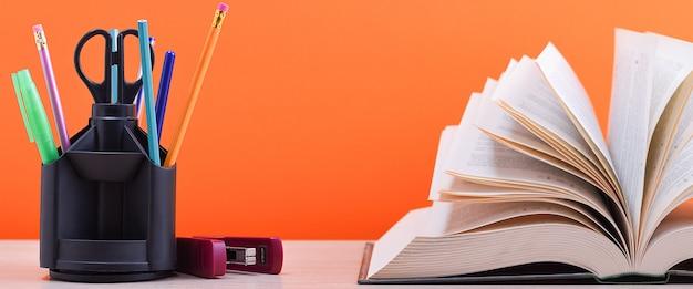 Un grande libro spesso con le pagine aperte come un fan e uno stand con penne e materiale scolastico