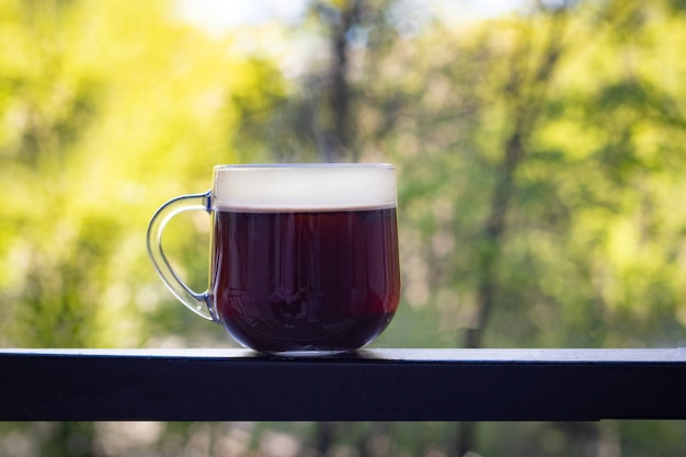 Una grande tazza trasparente con caffè nero si trova su un tavolo di ferro scuro su uno sfondo sfocato di alberi verdi estivi. buongiorno concetto. idee fresche. focalizzazione morbida.