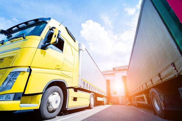 Grandi camion vicino al magazzino sullo sfondo del cielo blu