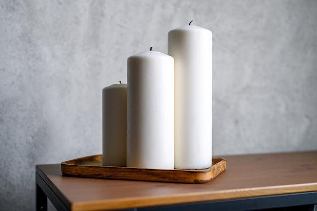 Grandi candele bianche nuove in un supporto di legno