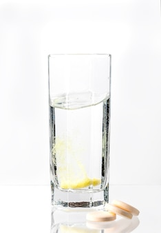 Una grande compressa bianca con si dissolve in un bicchiere d'acqua su uno sfondo bianco vitamina c