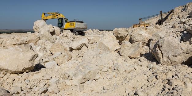 Un grande escavatore cingolato giallo sta estraendo roccia in una cava.