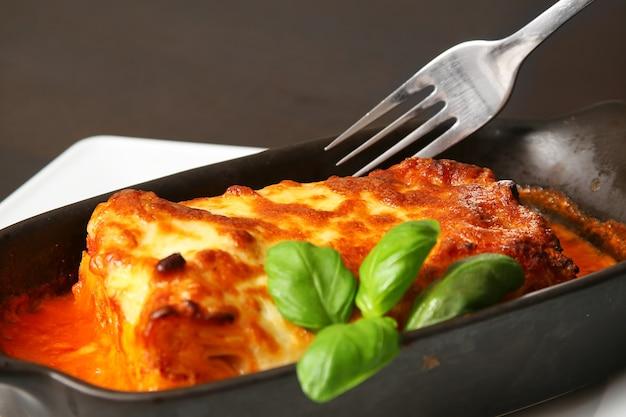 Lasagne alla bolognese con la forchetta d'argento sul tavolo di legno