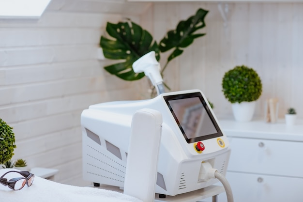Macchina per la depilazione laser in armadio bianco con piante verdi.