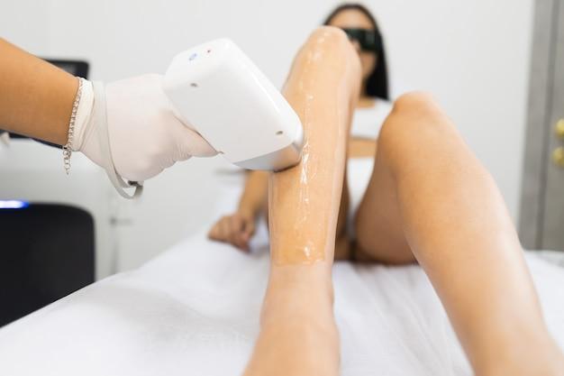 Depilazione laser dalle gambe della donna