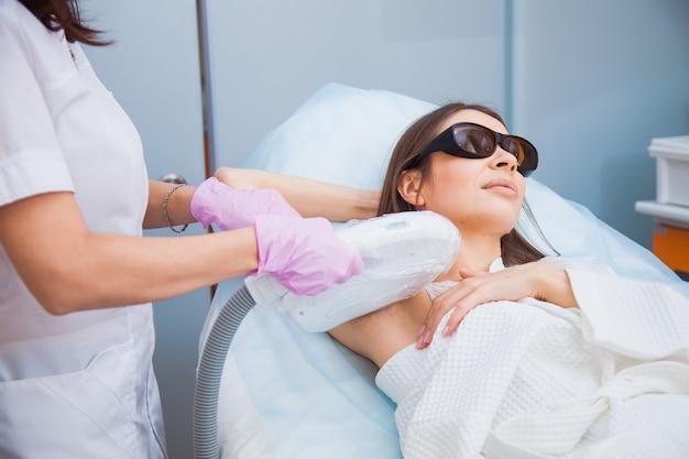Depilazione laser, fotoepilazione, concetto di cura del corpo e della pelle. giovane donna rimuovere i peli sulle ascelle presso la clinica di cosmetologia. colpo del primo piano, concetto di procedura di igiene