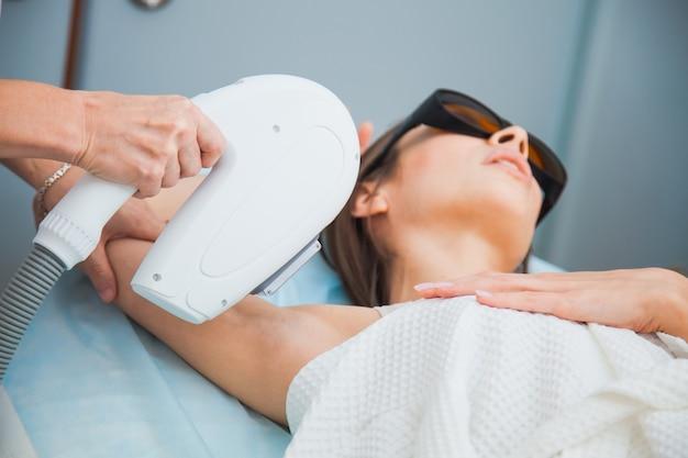 Depilazione laser, fotoepilazione, concetto di cura del corpo e della pelle. giovane donna rimuovere i peli sulle ascelle presso la clinica di cosmetologia. colpo del primo piano, femmina irriconoscibile