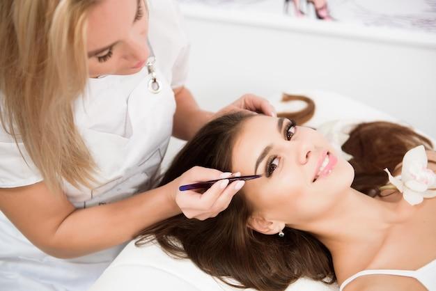 Estensione delle ciglia da lashmaker professionista in un salone di bellezza. donna sdraiata sul coach cosmetologico durante l'allargamento delle ciglia.