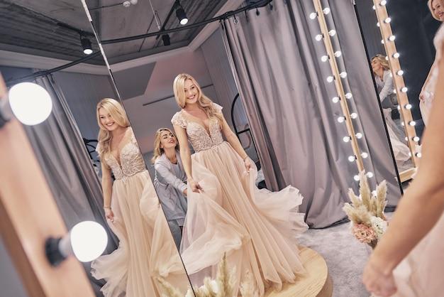 Ultimi dettagli. riflessione di una giovane donna attraente che aggiusta un abito da sposa su una sposa mentre sta in piedi nel camerino