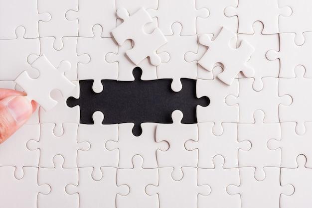 Ultimo pezzo gioco di puzzle di carta bianca ultimi pezzi messi a posto per risolvere il problema completa la missione