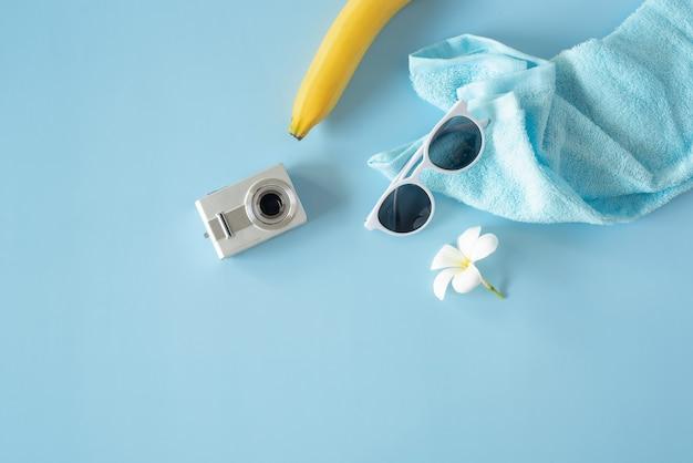 Lat ha messo gli accessori da viaggio nel nuovo stile normale con le macchine fotografiche occhiali banane e un asciugamano posizionato