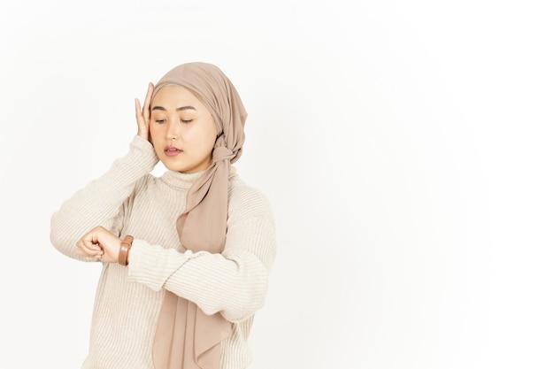 In ritardo e guardando l'orologio della bella donna asiatica che indossa l'hijab isolato su sfondo bianco