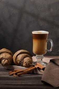 Late macchiato in un bicchiere alto su un vassoio di legno late con cannella e croissant appena sfornati