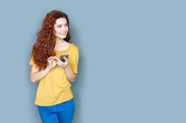 Ultimo smartphone. felice giovane donna positiva che sorride e che osserva da parte mentre utilizza il suo gadget digitale