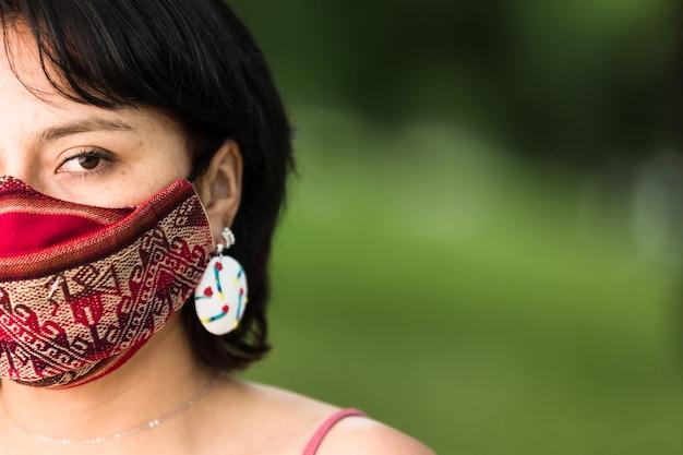 Donna boliviana dell'america latina con maschera in tessuto tradizionale maschera facciale in tessuto nativo quechua fatta a mano per la protezione del coronavirus covid19