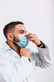Medico o dentista maschio adulto latinoamericano che indossa o si toglie una maschera chirurgica