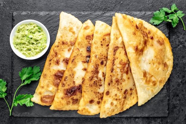 Empanadas fritte latinoamericane con avocado su un tavolo di pietra