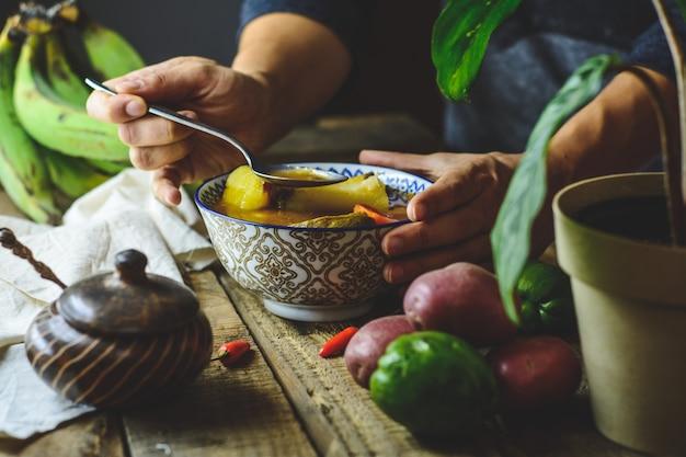 Zuppa di verdure latinoamericana, mani che afferrano il piatto. ingredienti carota, chayote, patata dolce, pepe verde banana.