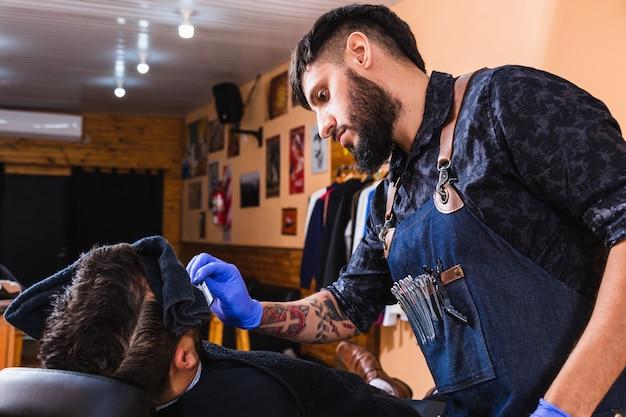 Barbiere latino. negozio di barbiere con barbiere che lavora. concetto di bellezza e benessere.