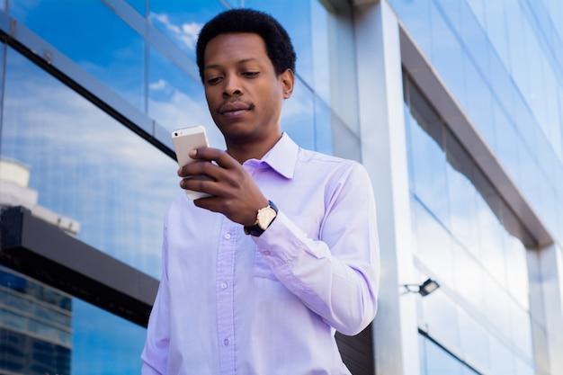Uomo d'affari latino che utilizza telefono cellulare nella città.