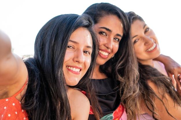 Amici latini che scattano una foto amiche ispaniche felici che sorridono alla telecamera per i social media