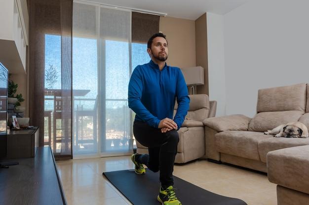 L'uomo latino, facendo un allenamento nel suo salotto, fa addominali, allungamenti e squat