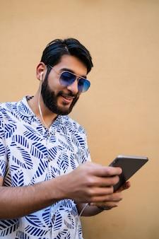 Uomo latino che per mezzo della sua compressa digitale con le cuffie