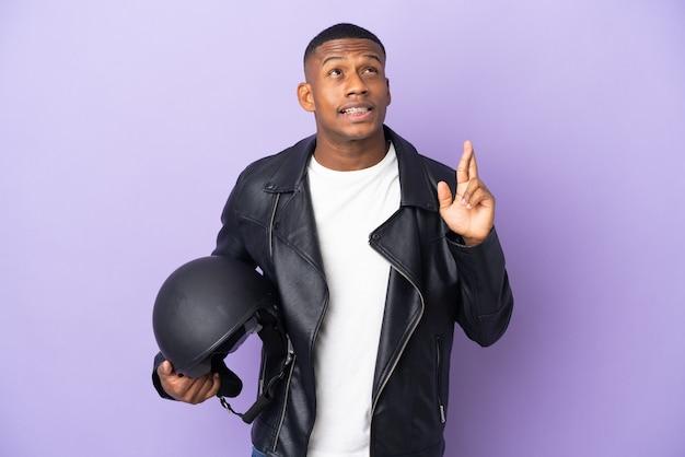 Uomo latino con un casco da motociclista isolato sulla parete viola con le dita incrociate e augurando il meglio
