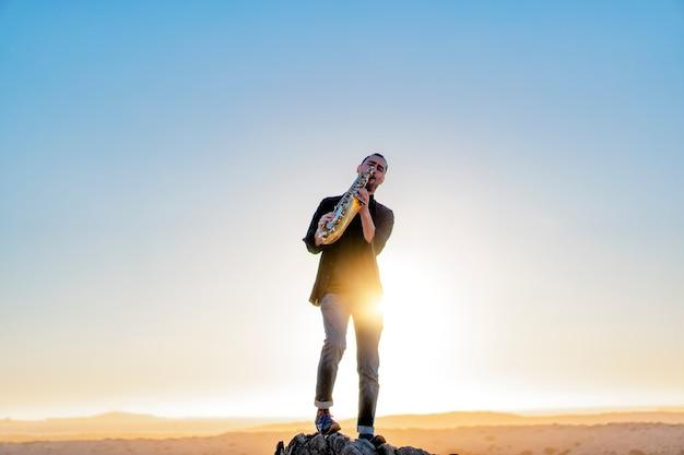 Musicista latino che suona il sassofono nel deserto di atacama in cile