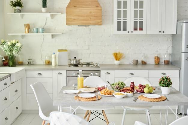 Colazione in stile latino sul tavolo. interno bianco luminoso moderno della cucina con i dettagli di legno e bianchi. mattina, idee per la colazione, concetto di interior design