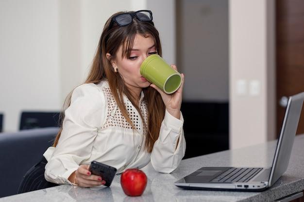 Donna latina che beve caffè mentre controlla il suo concetto di cellulare di essere a casa