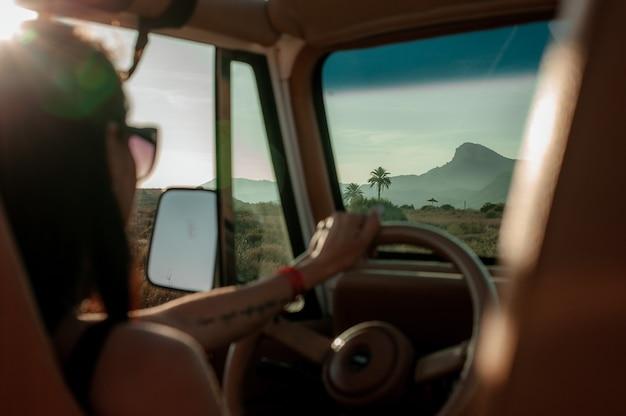 Donna latina alla guida di un veicolo 4x4 attraverso il deserto