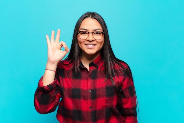 Donna latina che si sente felice, rilassata e soddisfatta, mostrando approvazione con un gesto ok, sorridendo