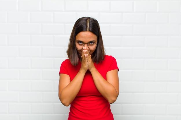 Donna latina che si sente preoccupata, fiduciosa e religiosa, pregando fedelmente con i palmi premuti, chiedendo perdono