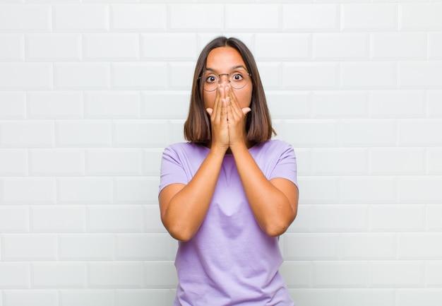Donna latina che si sente preoccupata, sconvolta e spaventata, coprendosi la bocca con le mani, sembrando ansiosa e avendo incasinato