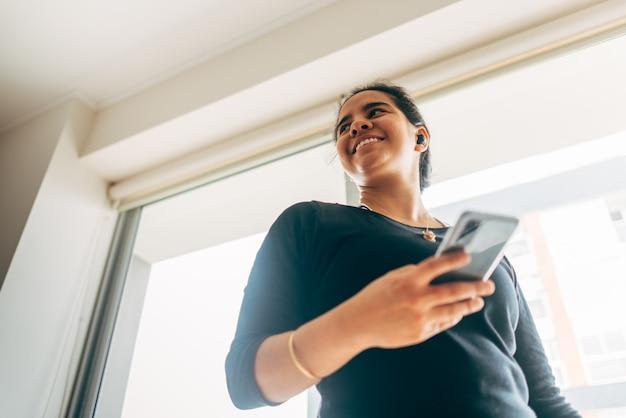 La donna latina a casa sorride mentre ascolta la musica con le sue cuffie dal suo smartphone. copia spazio