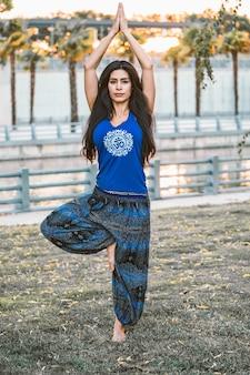 Una donna latina in abiti indiani fa una postura yoga in un parco al tramonto.