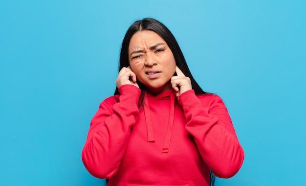 Donna latina che sembra arrabbiata, stressata e infastidita, coprendo entrambe le orecchie con un rumore assordante, un suono o una musica ad alto volume