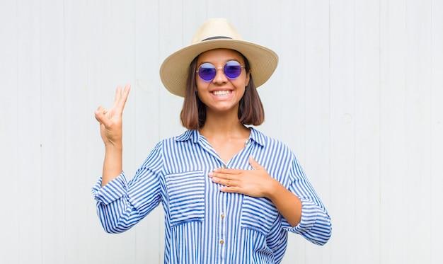 Donna latina che sembra felice, sicura e degna di fiducia, sorridente e mostrando segno di vittoria, con un atteggiamento positivo