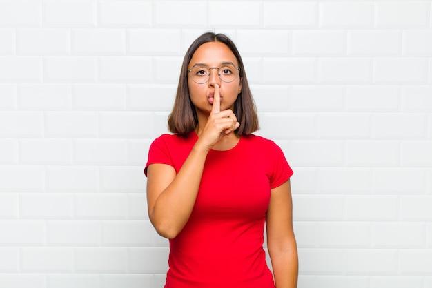 Donna latina dall'aspetto serio e arrabbiato con il dito premuto sulle labbra che chiede silenzio o silenzio, mantenendo un segreto