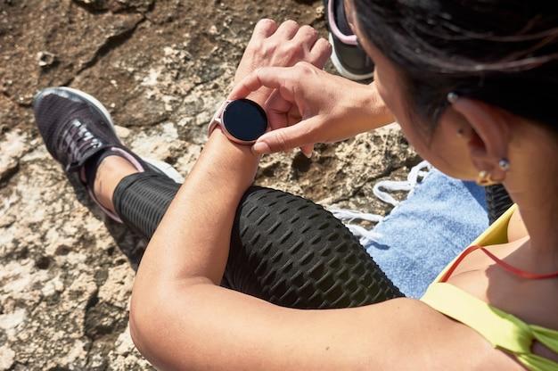 Donna latina, di mezza età, che riposa, riprende le forze, mangia, beve acqua, dopo una sessione di ginnastica