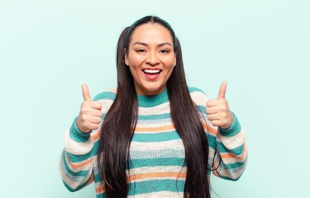 Donna latina che sorride ampiamente e sembra felice, positiva, sicura di sé e di successo, con entrambi i pollici in su