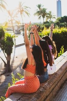 Donne latine di spalle tre amiche che si godono una giornata estiva ragazze felici alla moda