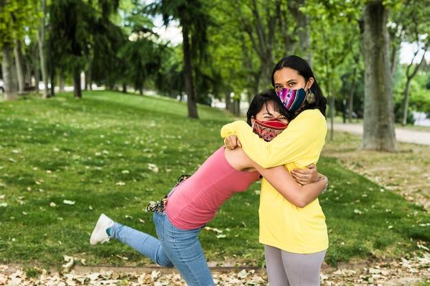 La giovane coppia lesbica latina gode della felicità in sud america bolivianlifestyle donna che indossa una maschera facciale di stoffa fatta a mano per coronavirus lgtbq