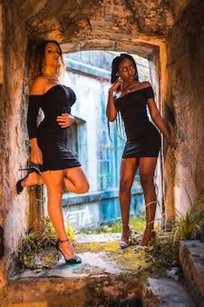 Donne latine e caucasiche in posa in abiti neri stretti e tacchi in una finestra di edificio