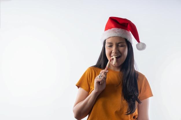Donna latina con cappello di babbo natale che mangia su un bastoncino di zucchero con gli occhi chiusi.