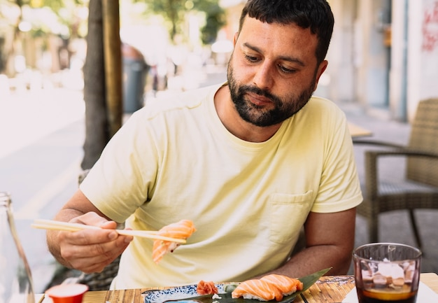 Ragazzo latino in maglietta gialla che mangia cibo giapponese
