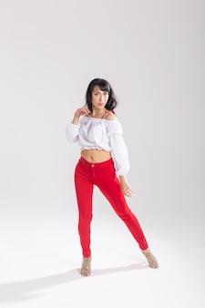 Danza latina, improvvisazione, concetto di danza contemporanea e di moda - giovane bella donna che balla su sfondo bianco studio