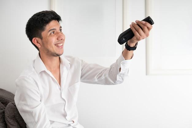 Uomo latino che cambia canale con il telecomando del televisore