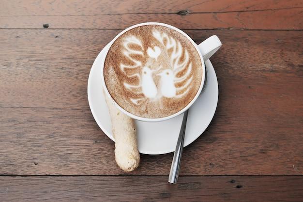 Caffè di arte del latte con un modello di due uccelli e biscotti in una tazza bianca su fondo di legno